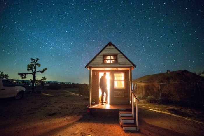 Tiny house on wheels shows in Joshua Tree under a sky full of stars