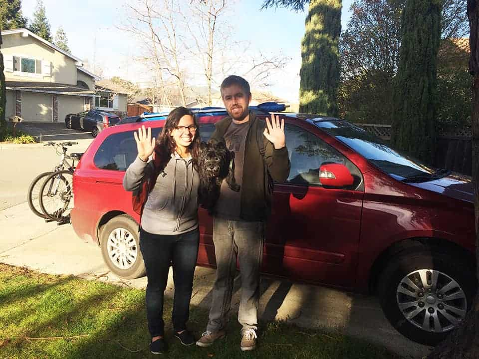 San Francisco couple waves in front of their minivan camper, which they converted into a travel pad for $700