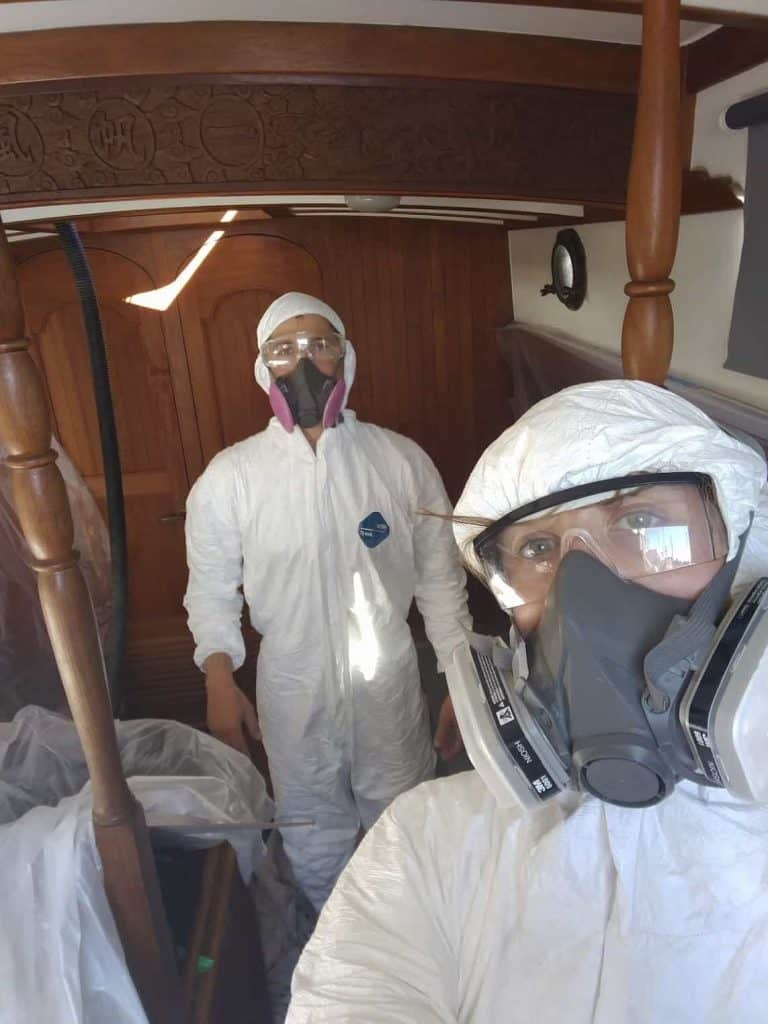 Tom and I wearing hazmat suits while living on a saiiboat