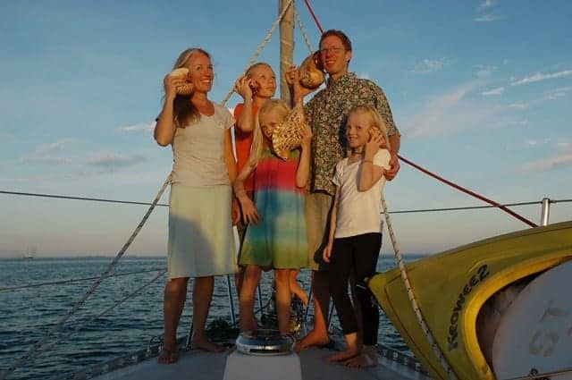 The family of Sailing Totem stands on the bow of their bluewater sailboat