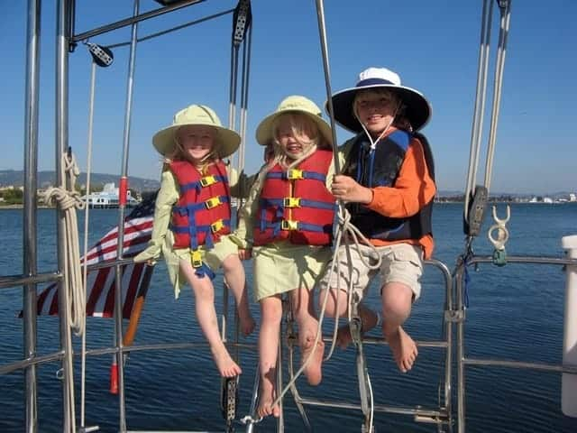 Three kids are perched on the side of a bluewater sailboat