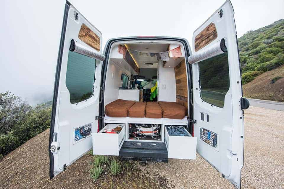 Back View Of A Sprinter Van Conversion With White Interior And Fold Down Bed In
