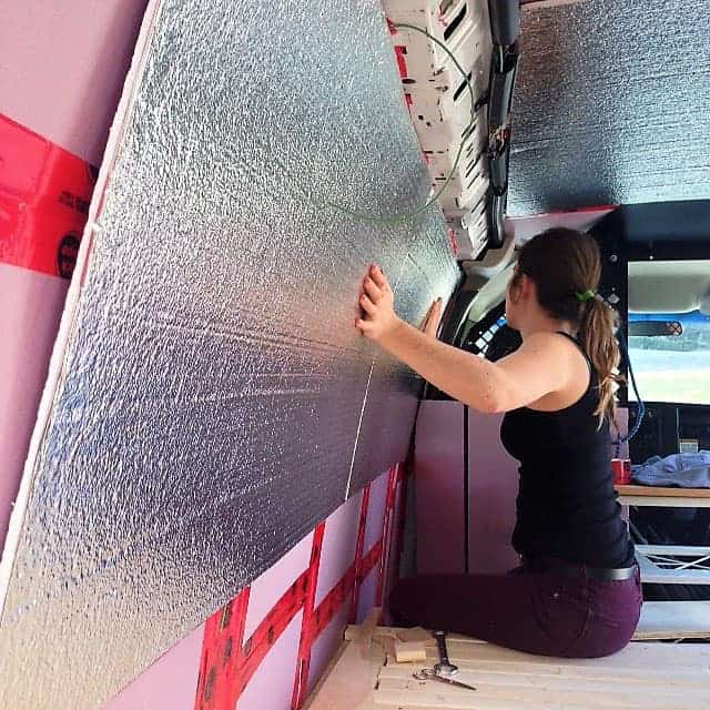 Woman installing insulation inside a campervan to keep heat in