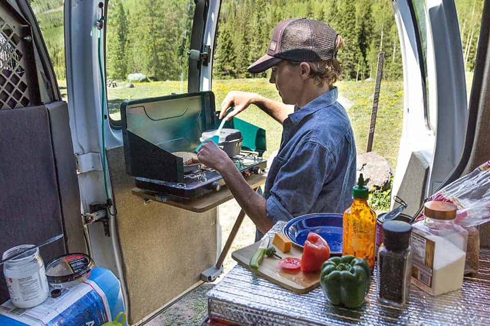 Cooking out of the back of a DIY camper van conversion is a breeze