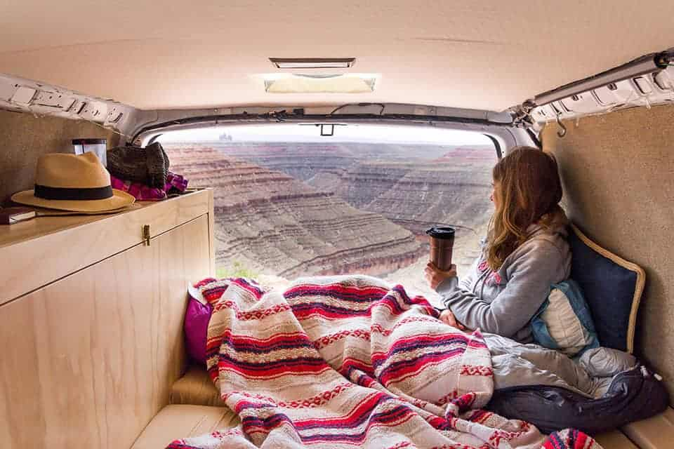 This Couple Spent Just 1000 On A DIY Camper Van Conversion Woman Sitting In Back