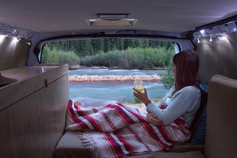 Women Drinks Wine While Looking Out At A Stream In Her DIY Camper Van Conversion