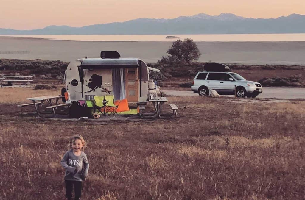 Travel trailer parked in a meadow with SUV in the distance and child playing