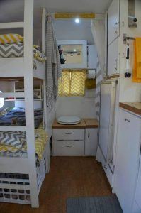 This interior view of the travel trailer features bunk beds and a composting toilet