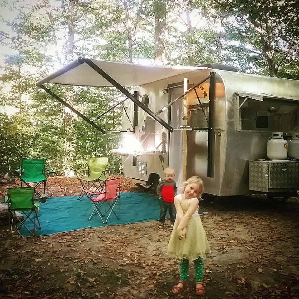 The kids play outside a tiny travel trailer while camping in the woods