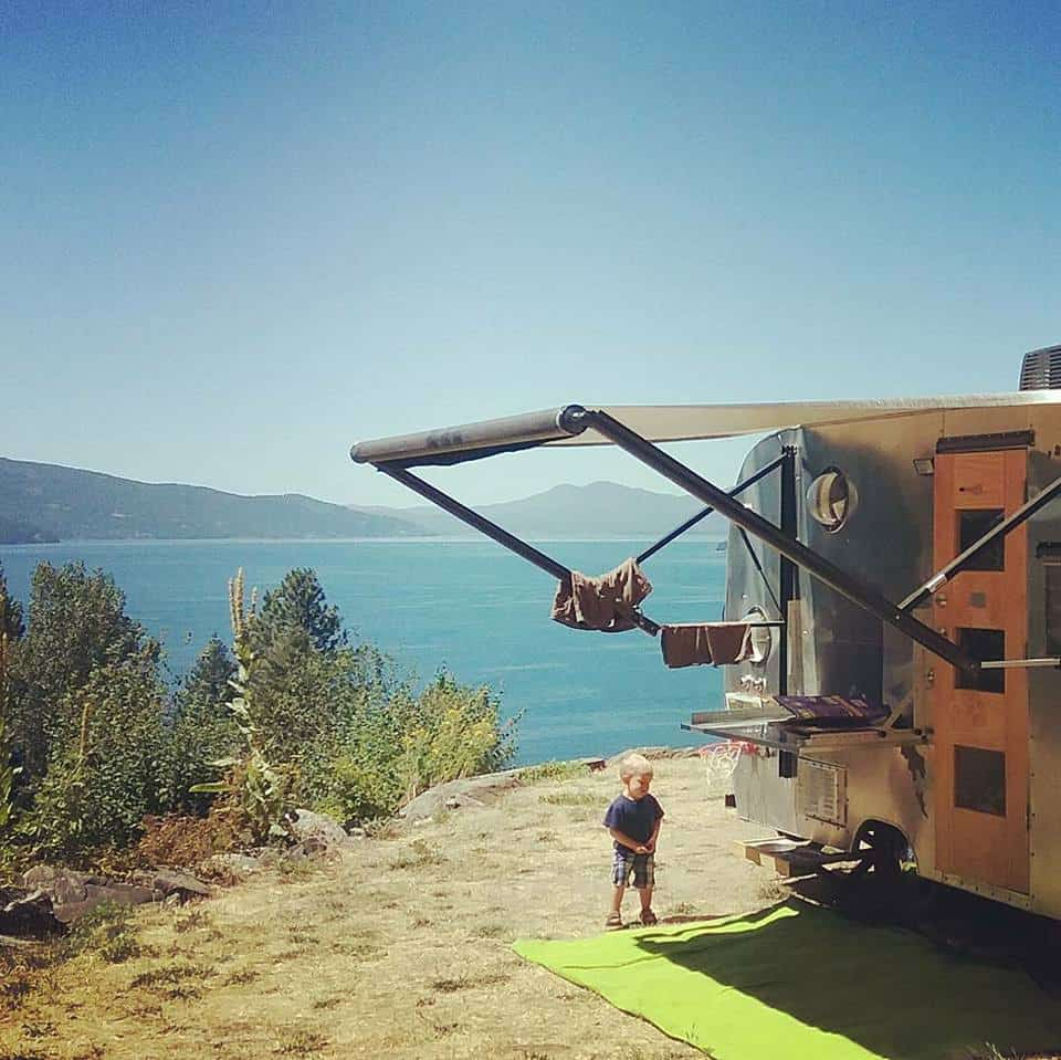Little boy plays outside a travel trailer parked on a cliff overlooking the beach