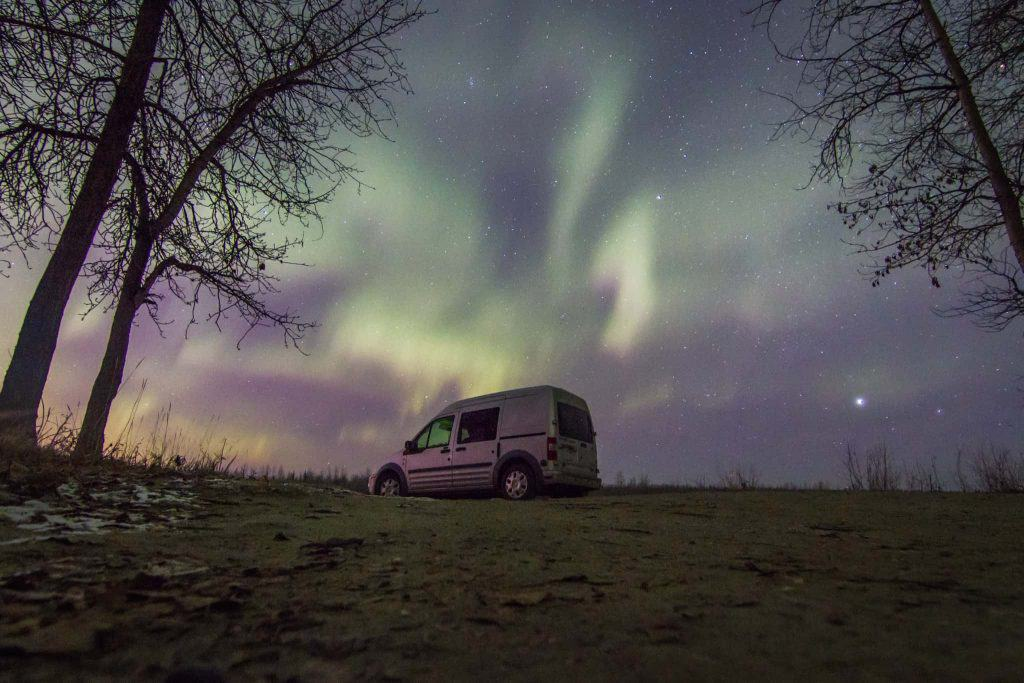 Ford Transit Connect camper van with the northern lights in the sky