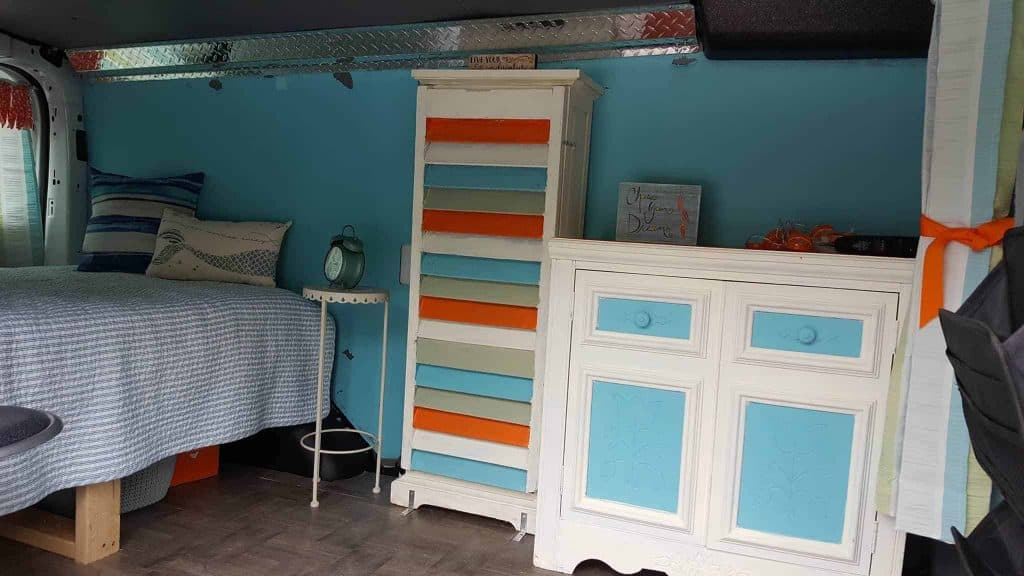 This Ford Transit camper van has whimsical colors, a bed and dresser