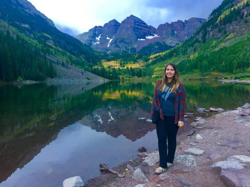 Sarah loves living in a van full-time. Hers is a Ford Transit Connect camper van. Here she poses at a beautiful alpine lake
