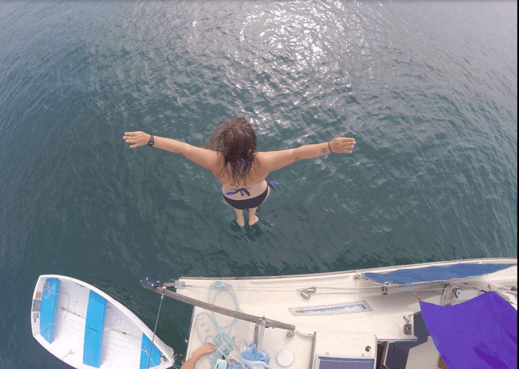 Elena jumps into the water from the deck of her catamaran sailboat