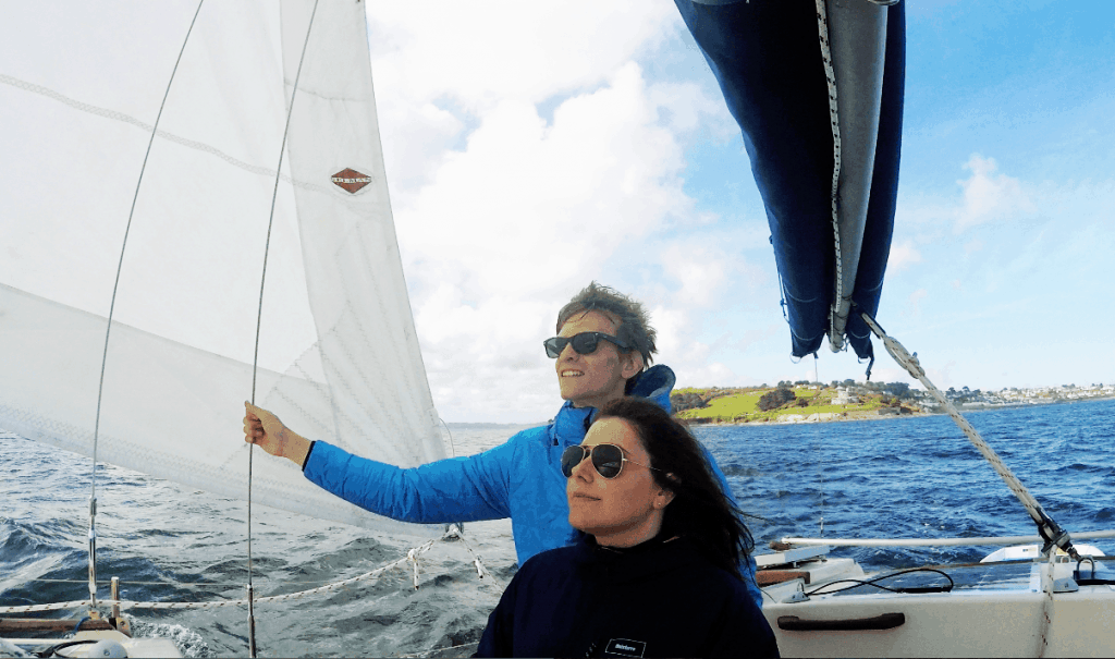 Elena and Ryan stand on the deck of their sailing catamaran