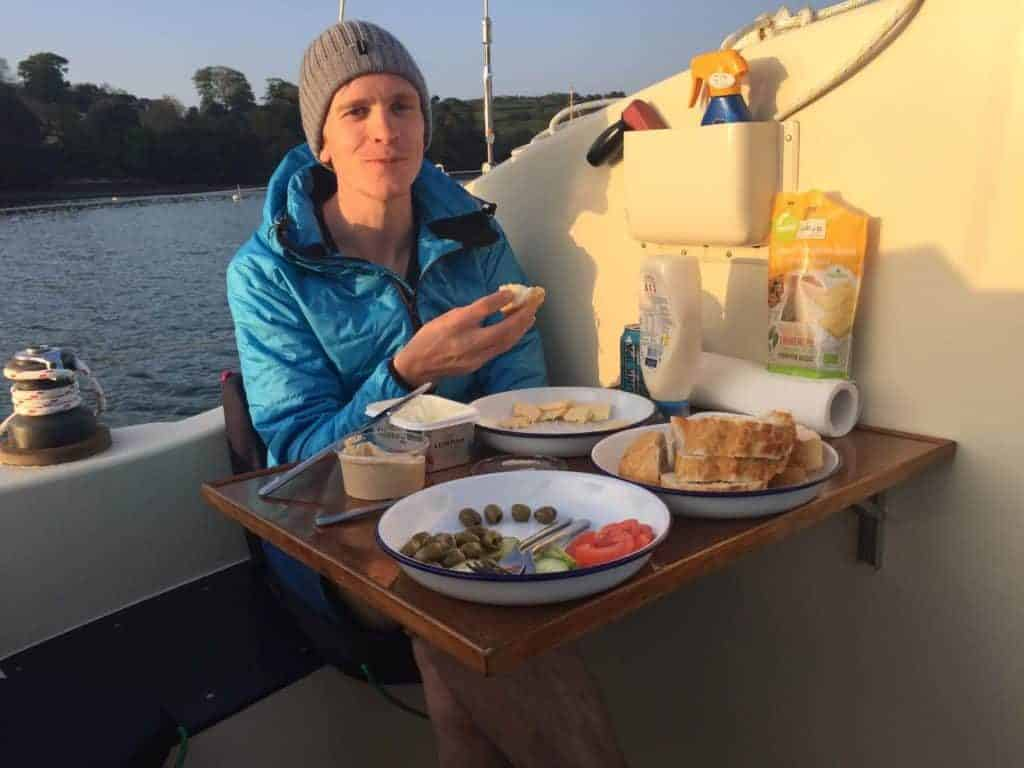 Ryan eats a meal on the deck of their sailing catamaran in the Mediterranean sea
