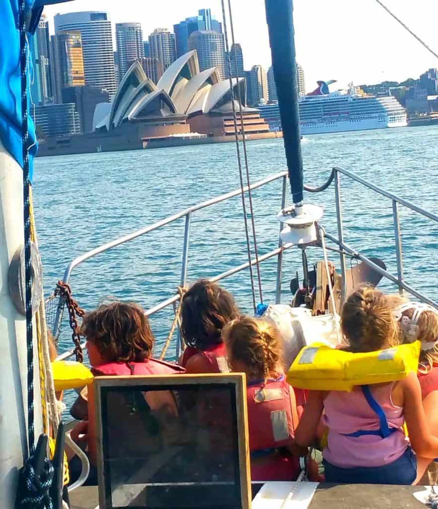 Children in life vests sitting at the bow of the their small sailing yacht, looking at Sydney, Australia.