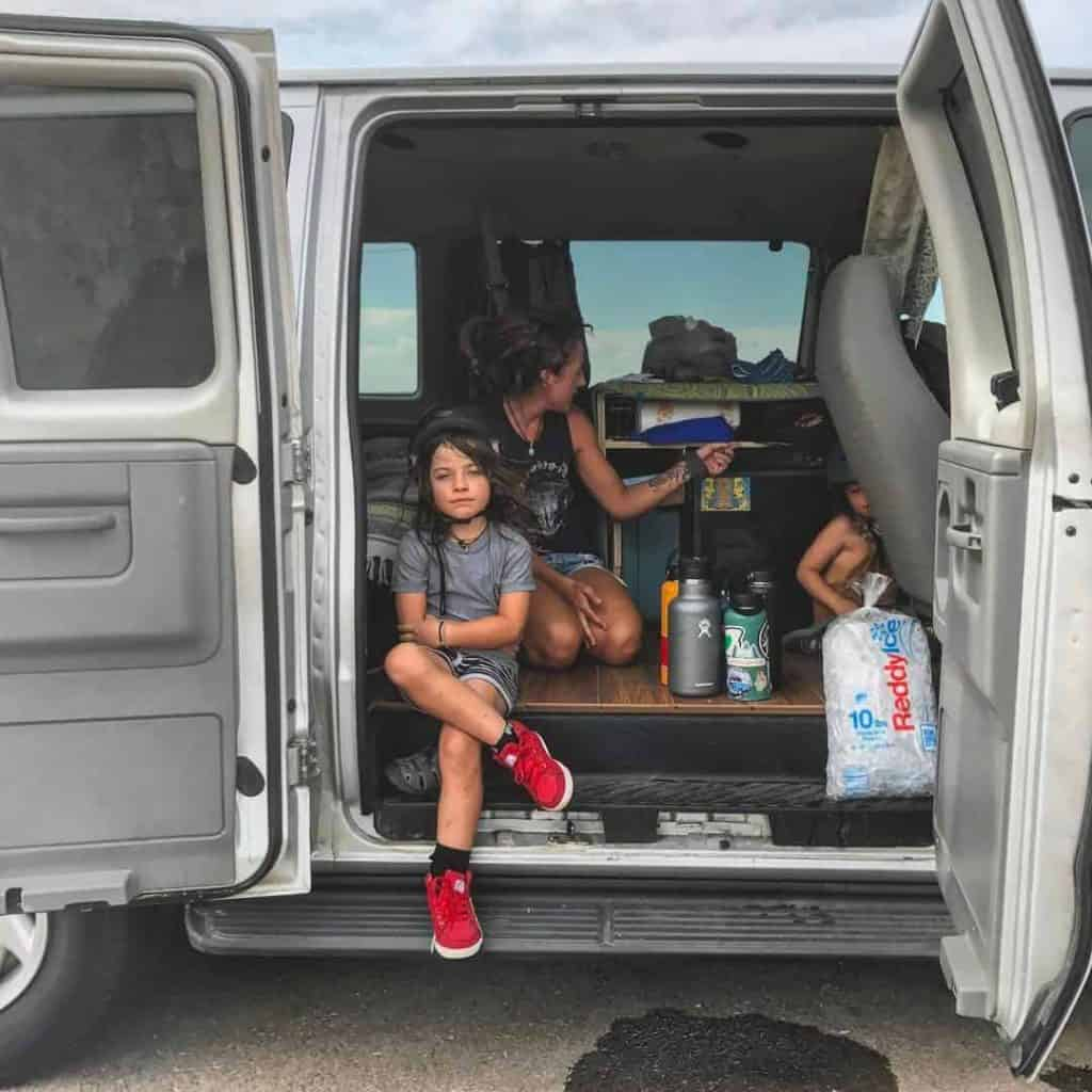 Two children and two adults are living in this van, while the oldest son prefers to sleep outside in a tent
