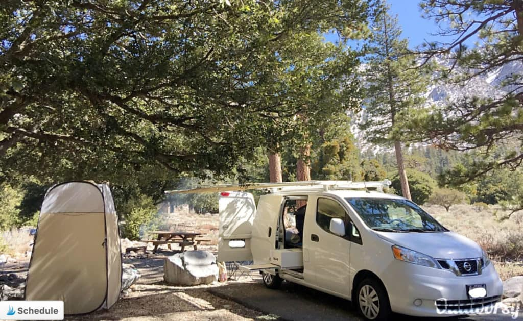 White Nissan campervan parked in a campground
