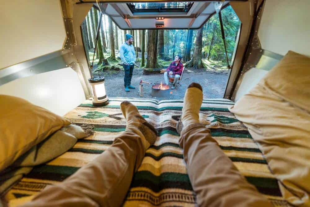 man's feet in the back of a camper van rental with Outdoorsy