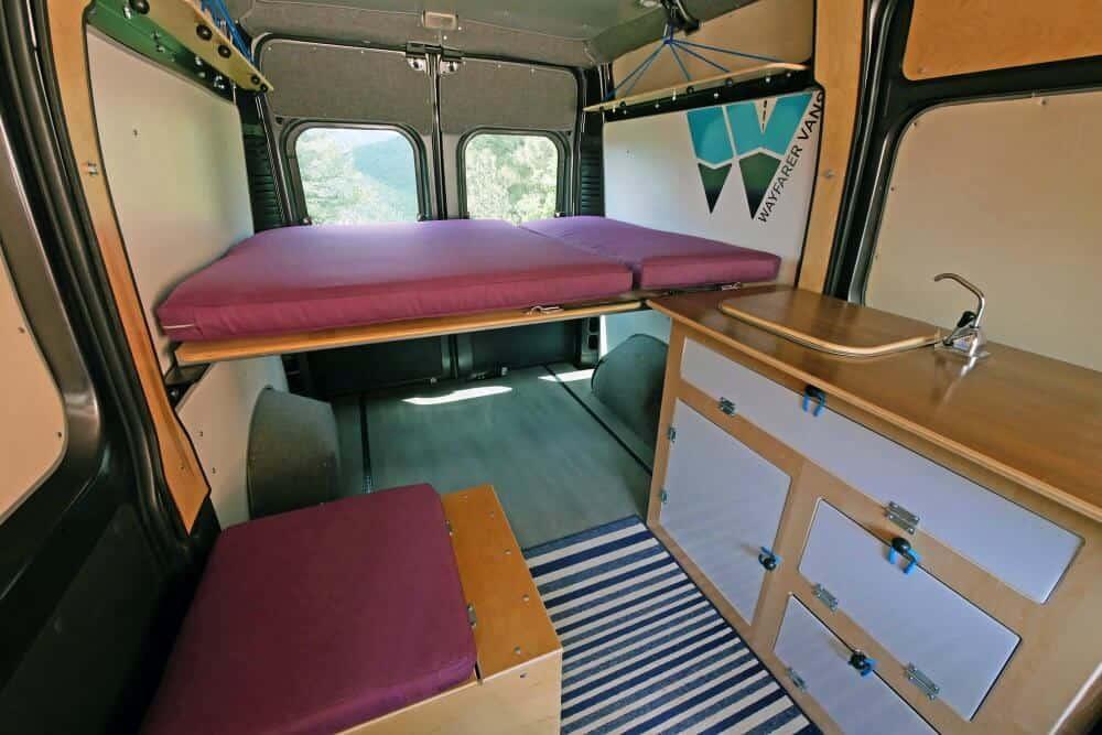 Dodge Ram Promaster campervan interior with platform bed, sink and seat.
