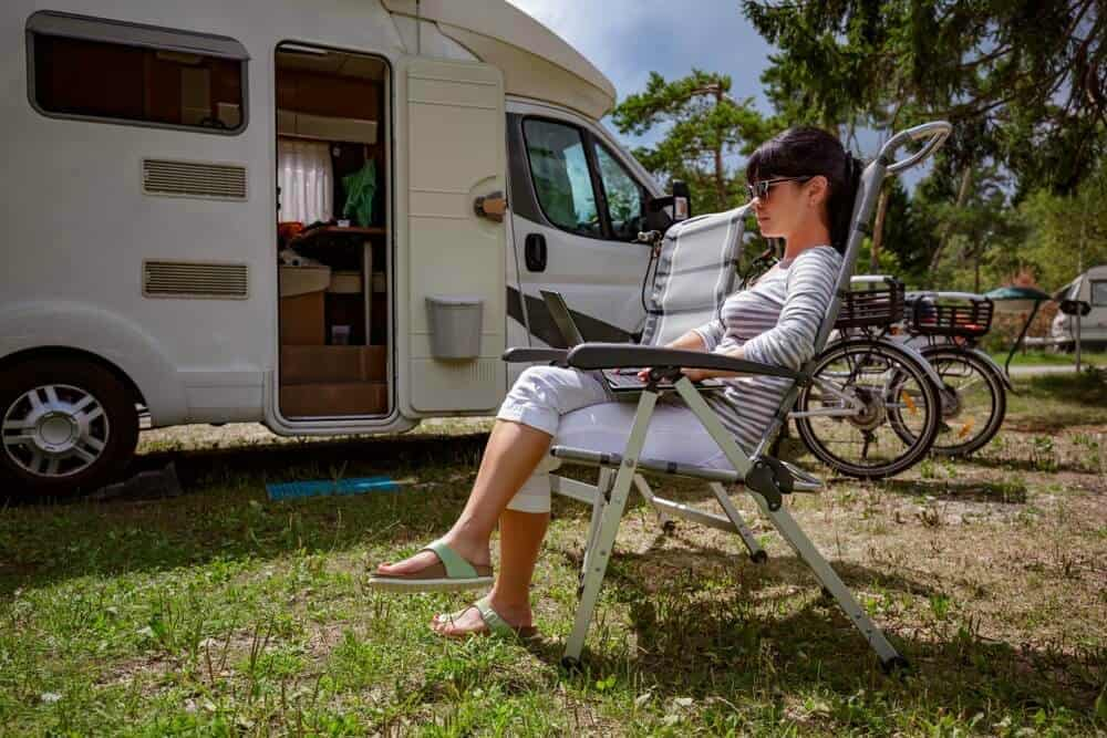 RVer working remotely from a laptop in front of her motorhome