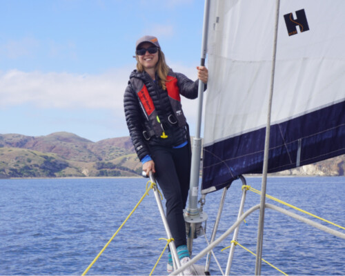 woman standing on a sailboat bow demonstrating what to wear sailing