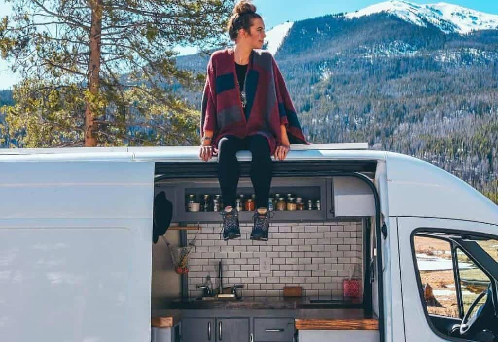 Sydney sits on top of her Sprinter conversion, which she built out for just $6,000