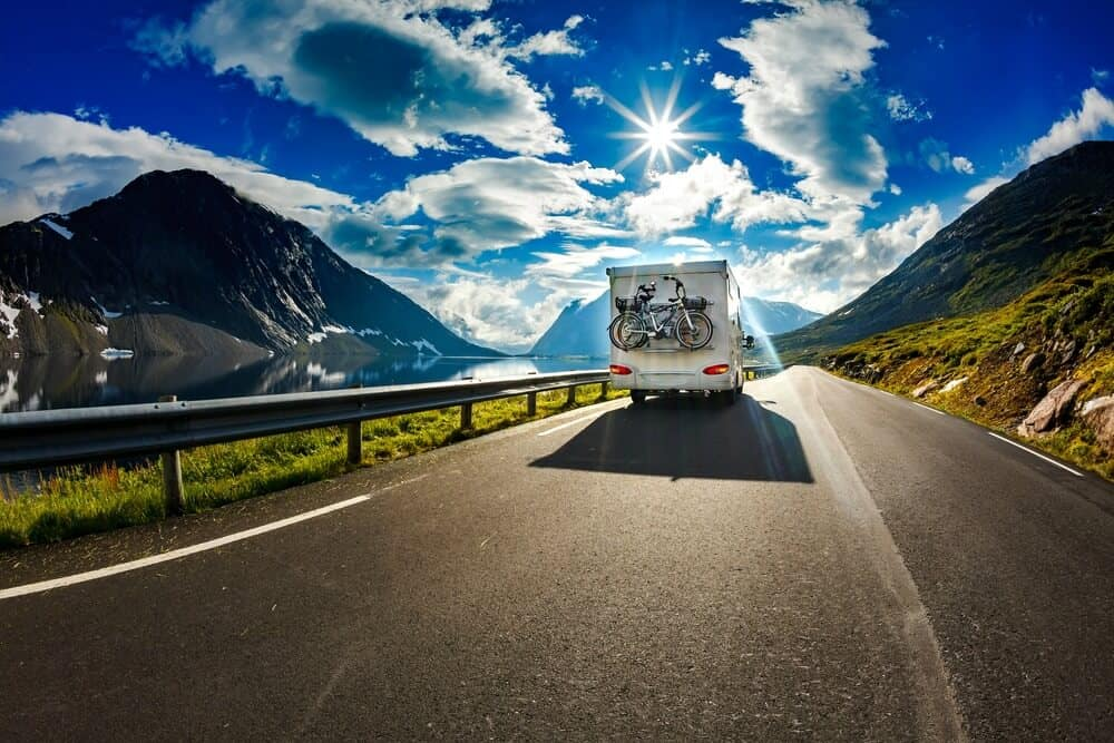 Motorhome travels down a scenic highway in the mountains. RV Share offers both private RV rentals and dealership camper rentals