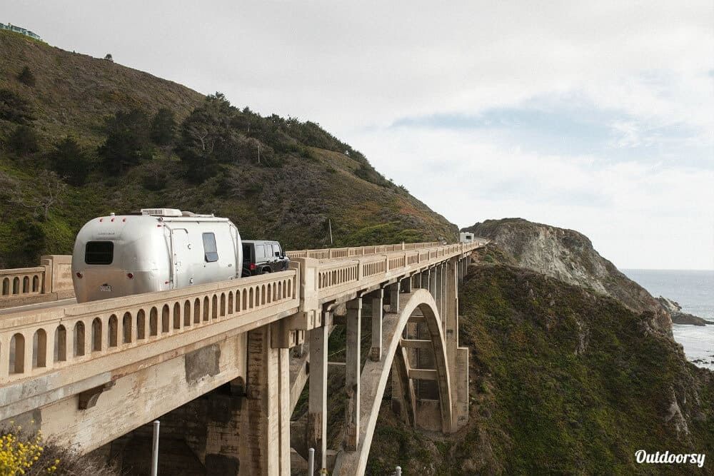 Airstream RV rental going over the bridge in Big Sur. Outdoorsy provides private RV rentals