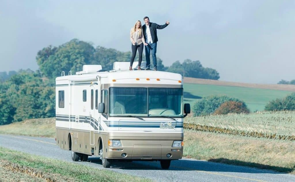 Emily and Hudson are Vipkid Teachers standing on top of their RV - a very popular van life job