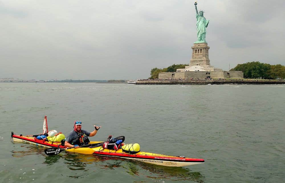 Rich Brand poses in his kayak in front of the statue of liberty