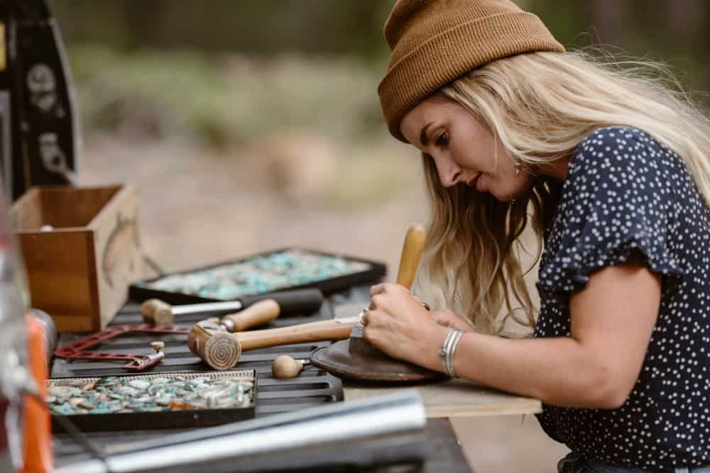 Madison works on jewelry from the back of her truck camper