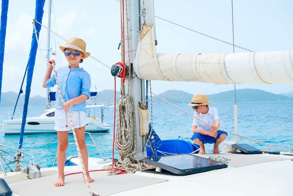 Kids standing on the deck of a sailboat - it's important to get traveler's insurance when leaving the U.S.