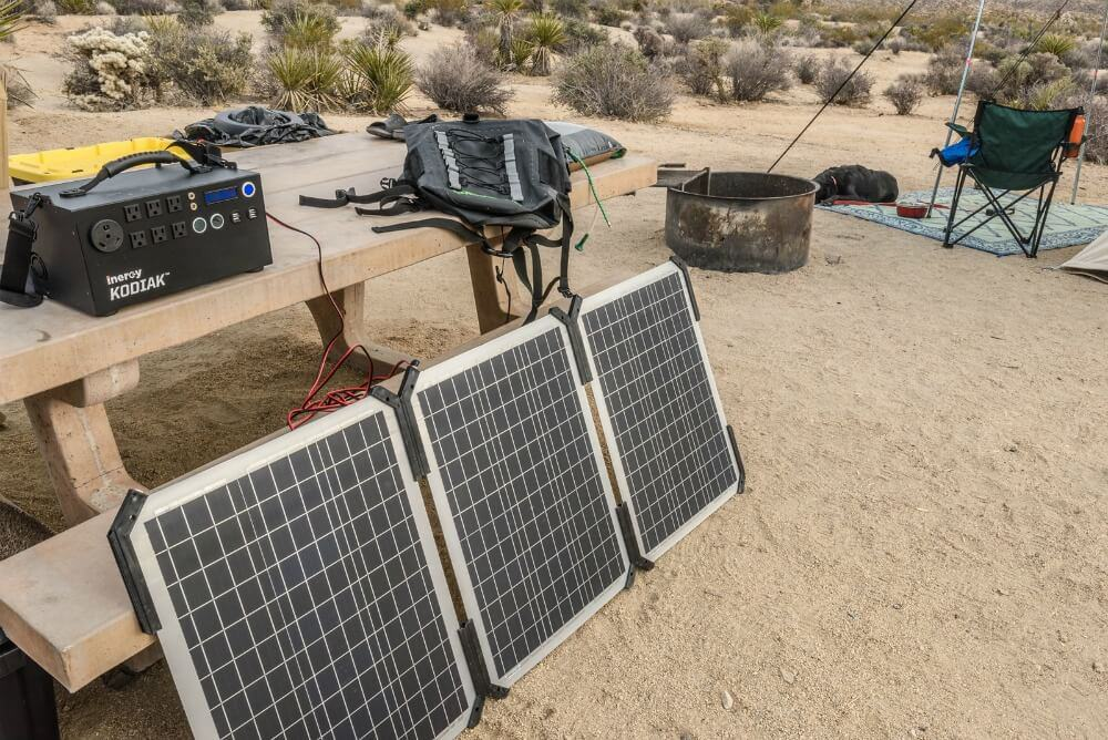 Solar panels charging the Inergy solar generator on a picnic table