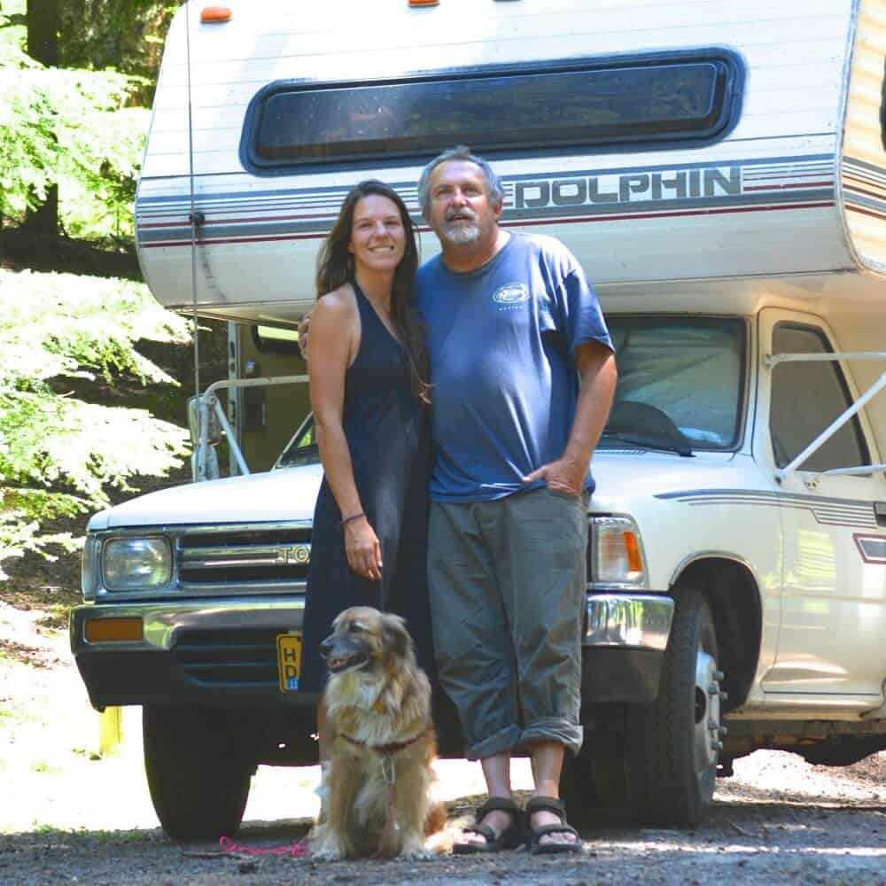 Tom and Brittany standing in front of their Toyota Dolphin RV