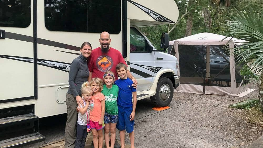 RVing family standing in front of their motorhome