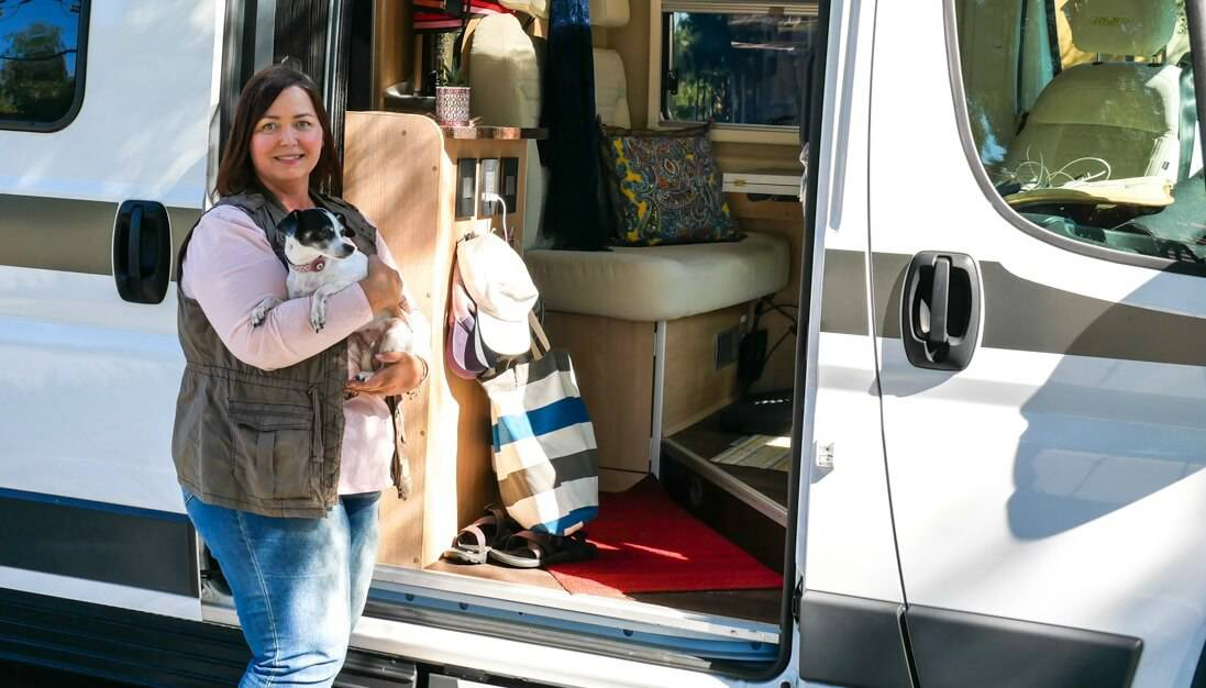 Amber and her dog pose in front of her RV campervan