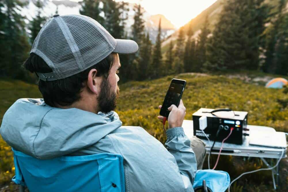 Man is camping in the mountains with a phone and computer plugged into a solar powered generator by Inergy
