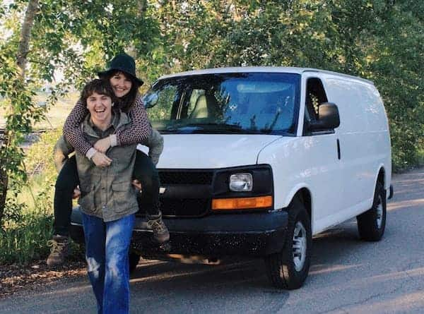 This white cargo van with a couple standing in front makes a perfect stealth camper van