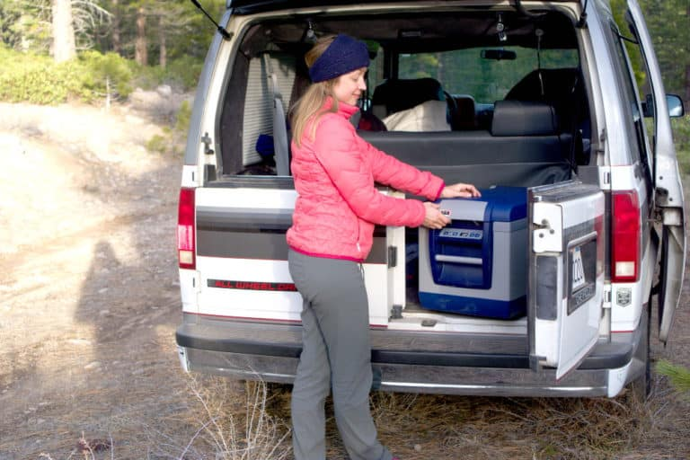 Woman with a 12 volt refrigerator in the back of her campervan