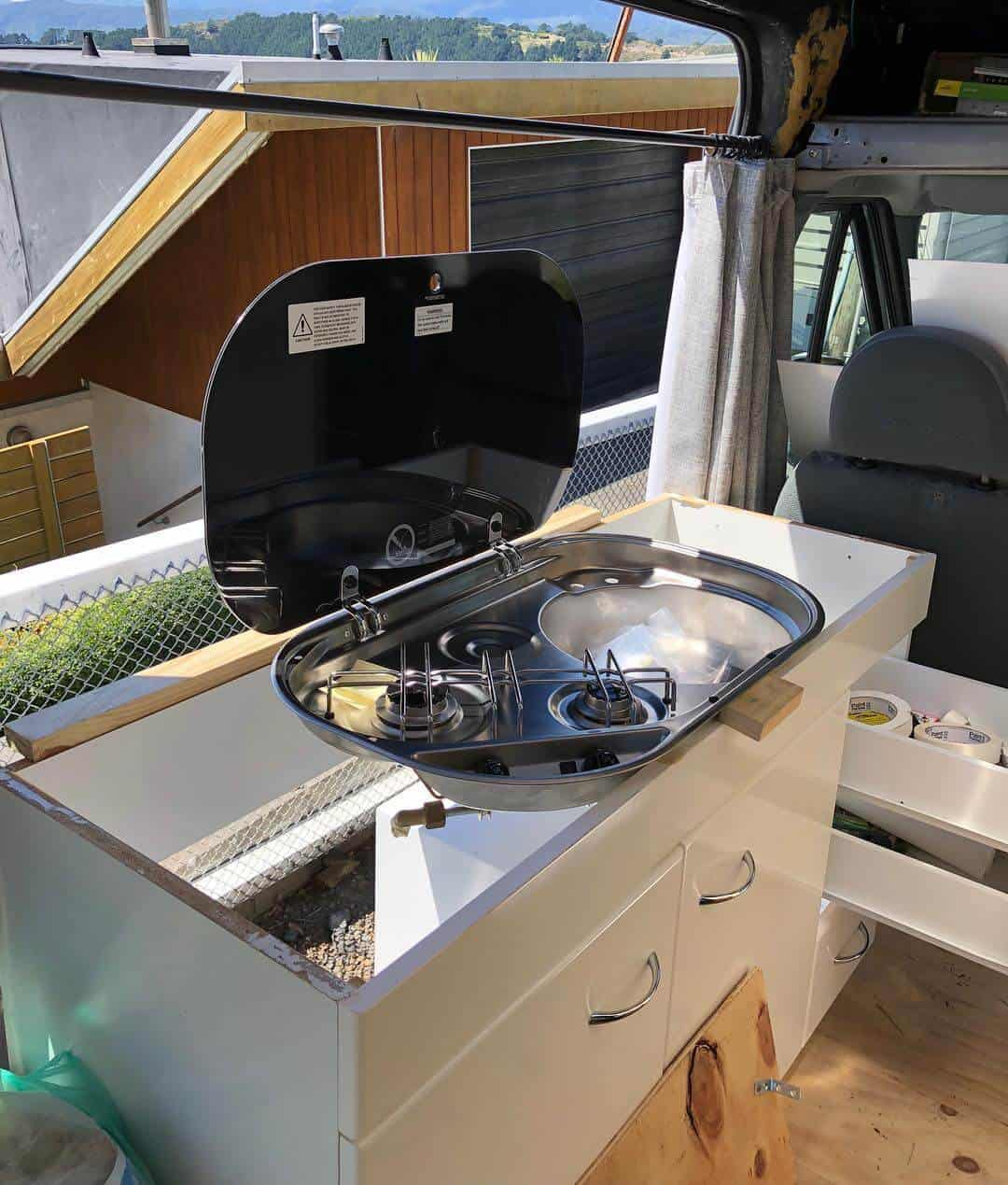 All-in-one campervan kitchen includes the sink, a faucet and a stove