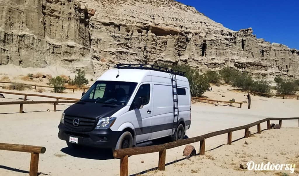 Mercedes Sprinter campervan on a beach with bluffs in the background