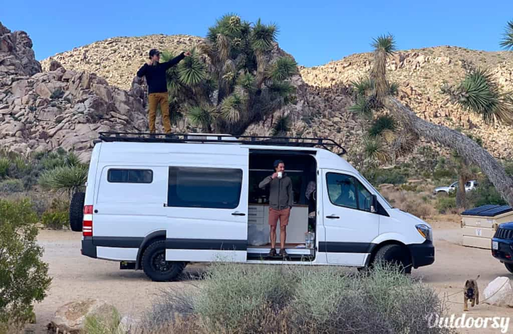Mercedes Sprinter conversion van parked at Joshua Tree with men standing inside