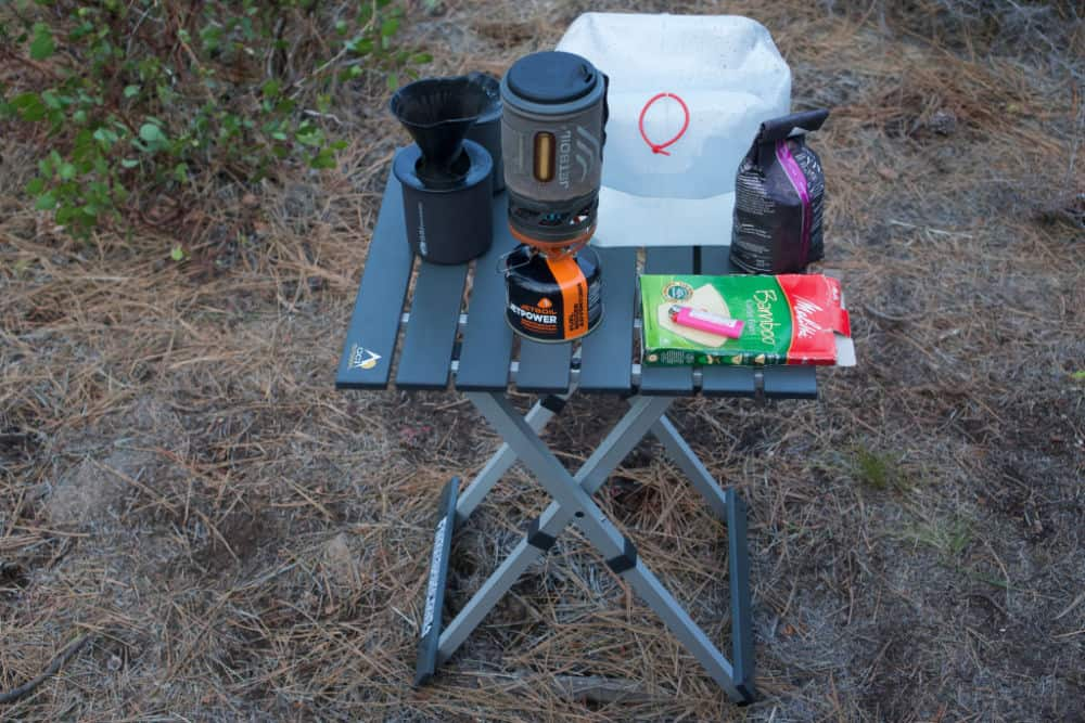 Portable camping table with coffee items and water