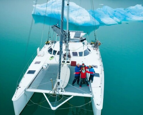 Beautiful catamaran sailboat shown floating near an iceberg