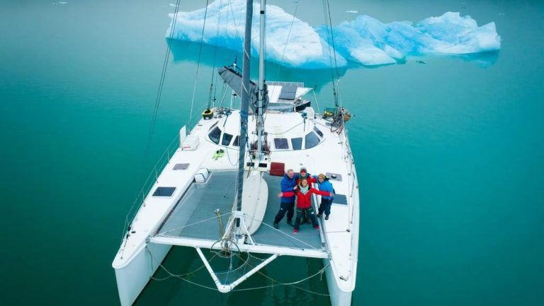 Beautiful catamaran sailboat shown floating near an iceberg