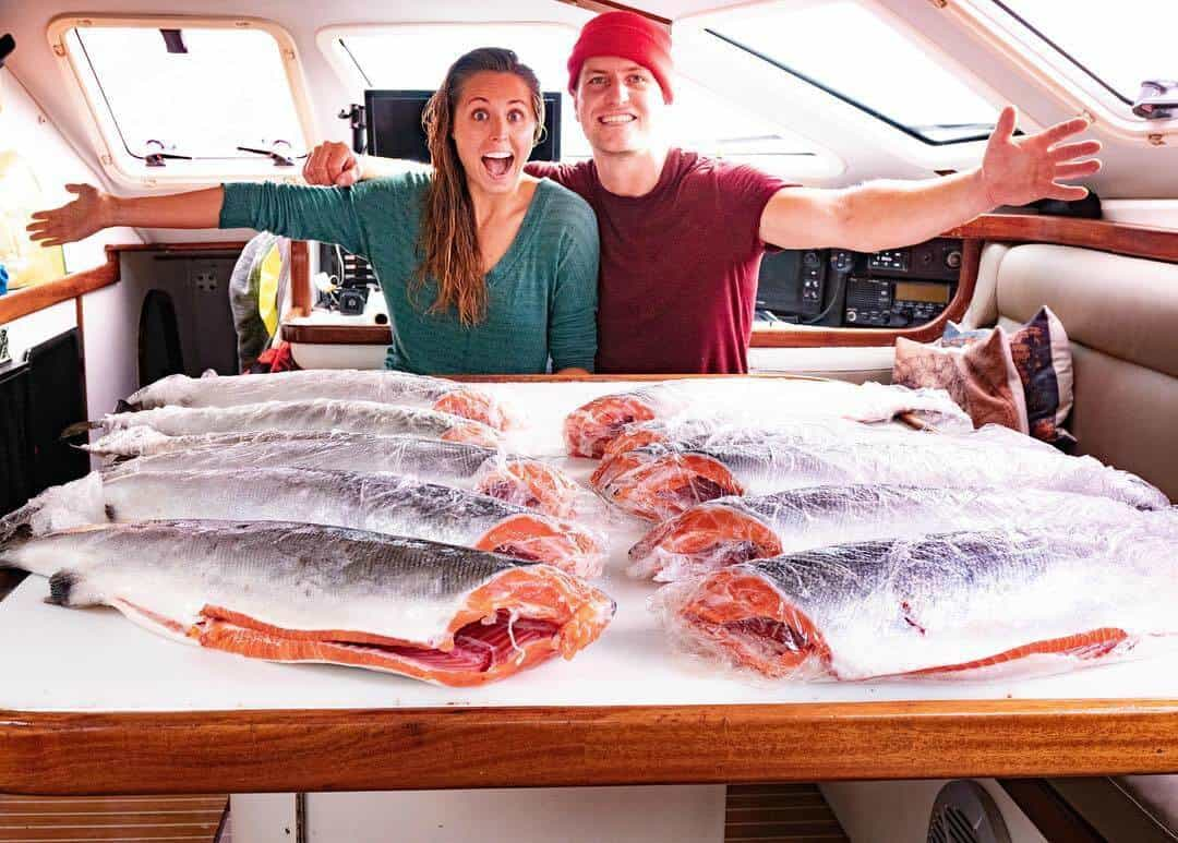 Morgan and Eric pose inside their cruising sailboat with a stock of fresh salmon