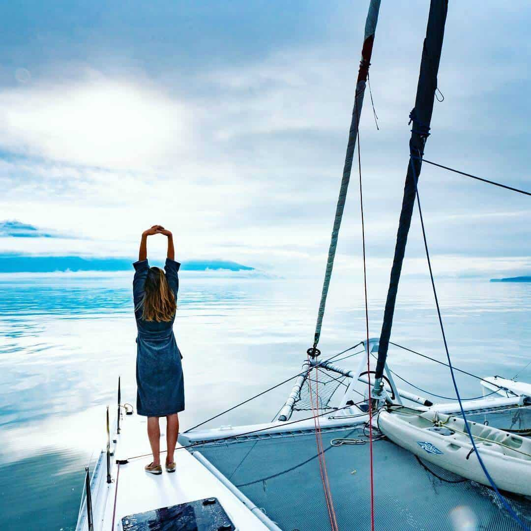 Morgan stretches on the forward deck of her catamaran sailboat in Alaska