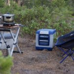 Folding camping chair seen with a folding table and fridge